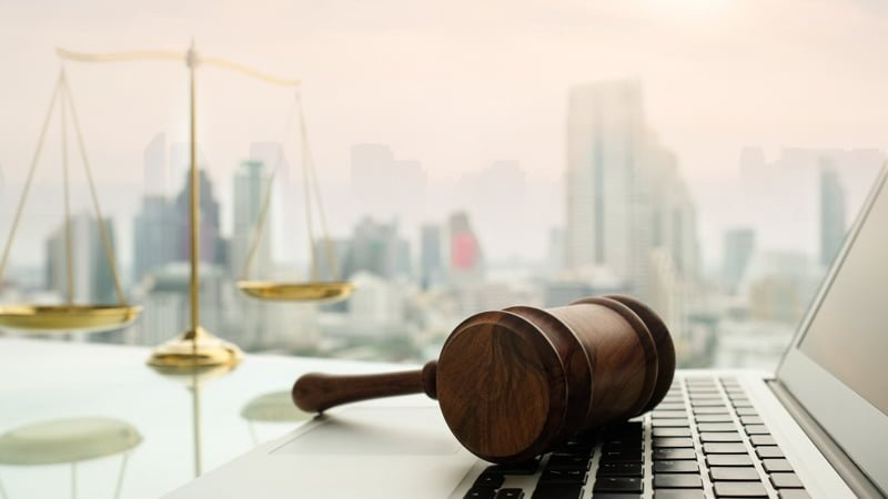Gavel on a Laptop Justice Scale and Buildings Background