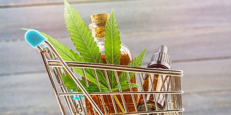 medical CBD oil and a cannabis leaf on a shopping cart