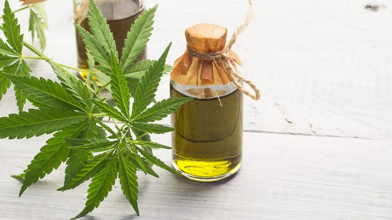Cannabis oil extract in a bottle with hemp leaves